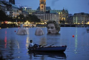 142975-man-in-a-rowing-boat-floats-near-a-mermaid-sculpture-created-by-oliver