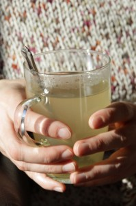 Hands holding lemon honey drink