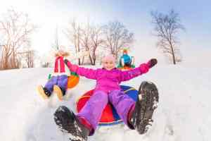 Girl and her friends sliding down hill on tubes