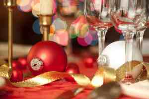 Red and white Christmas ornaments as table decorations, amidst wine glasses