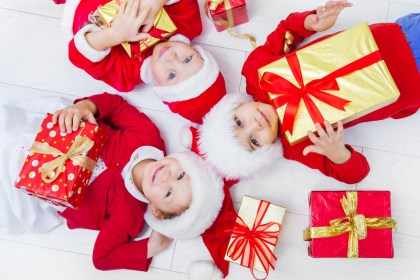 Group of three children in Christmas hat with presents on floor