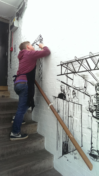 Roger Mason painting mural in Dalston