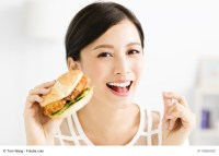 happy young woman eating big hamburger