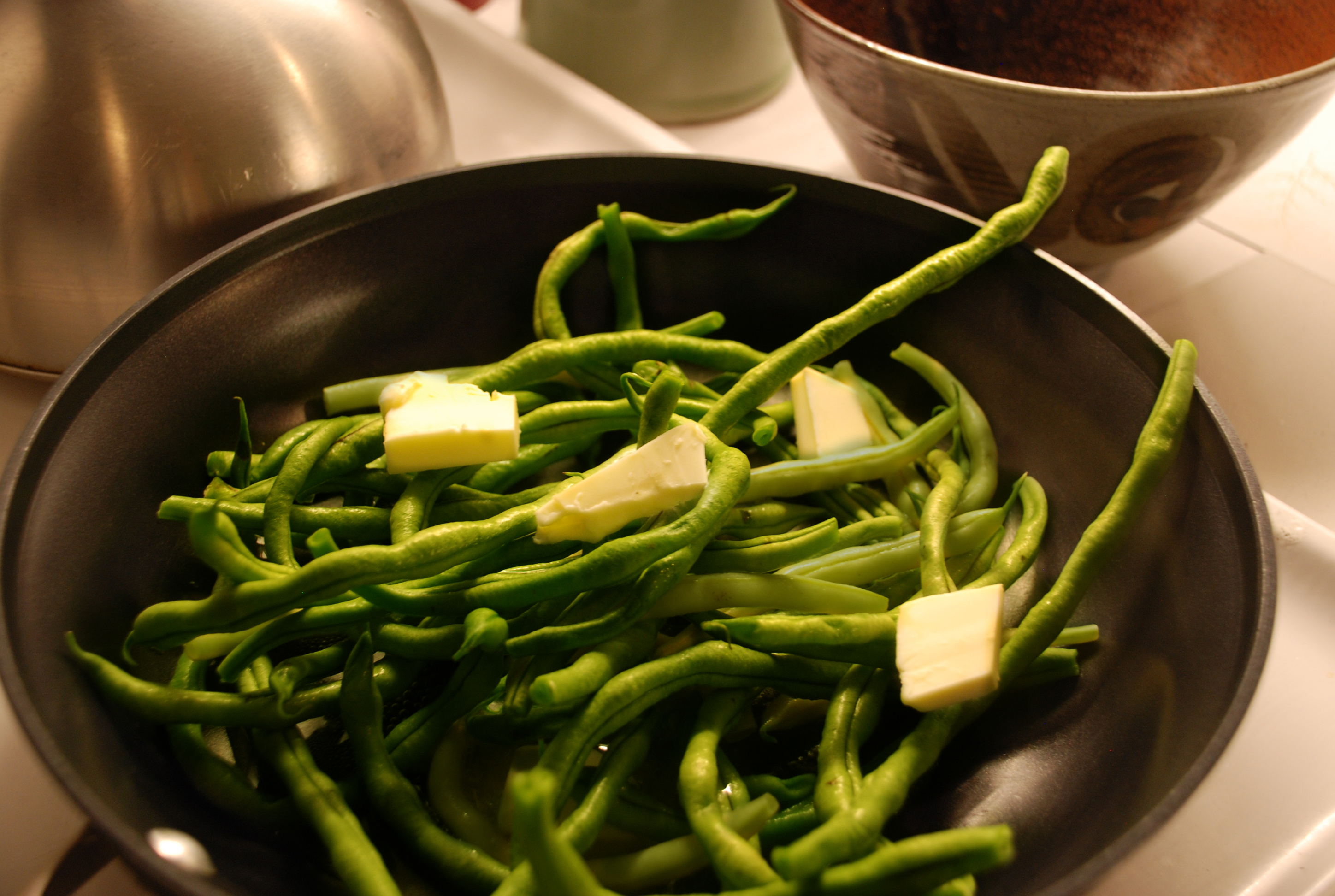 Green beans ready to cook with butter in a skillet.