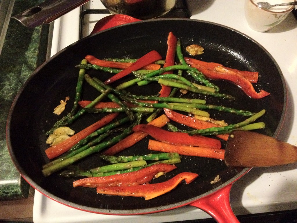 Asparagus and red peppers in a skillet.