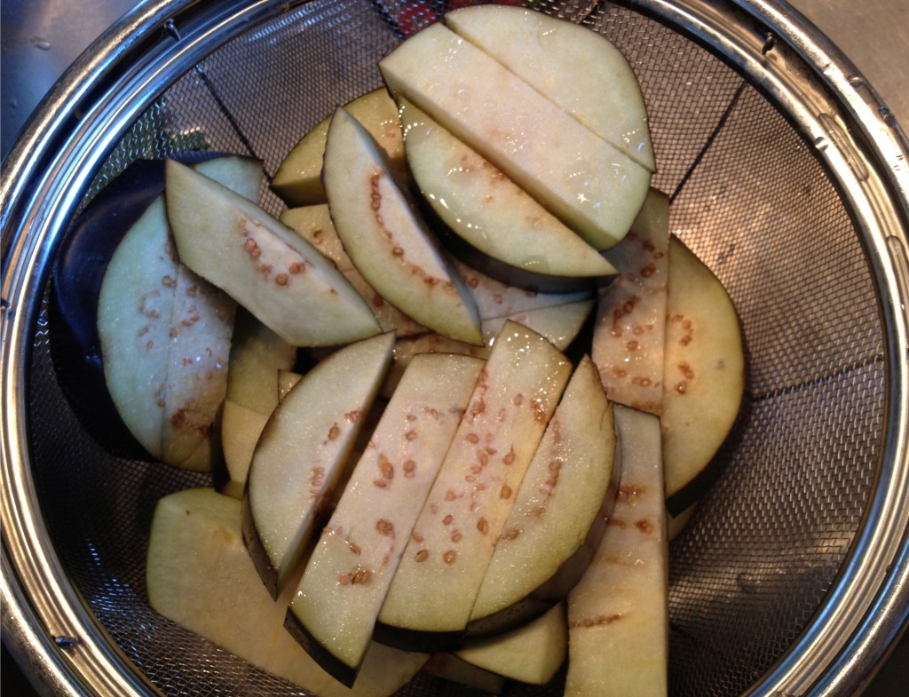 Salted eggplant in a colander.
