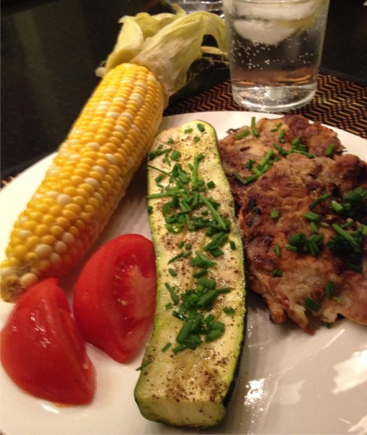 Soft shell crabs, corn on the cob, zucchini, and tomatoes on a white plate.