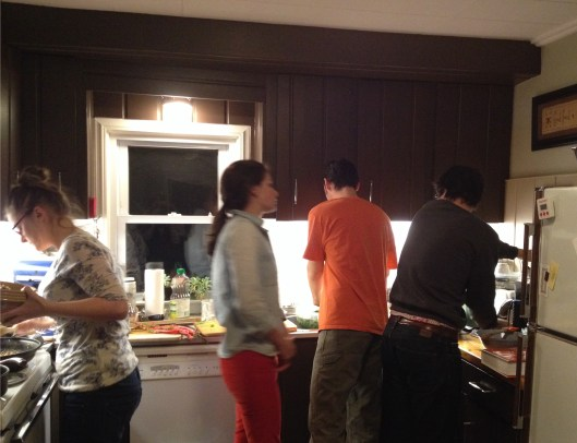 Four young adults cooking in a kitchen