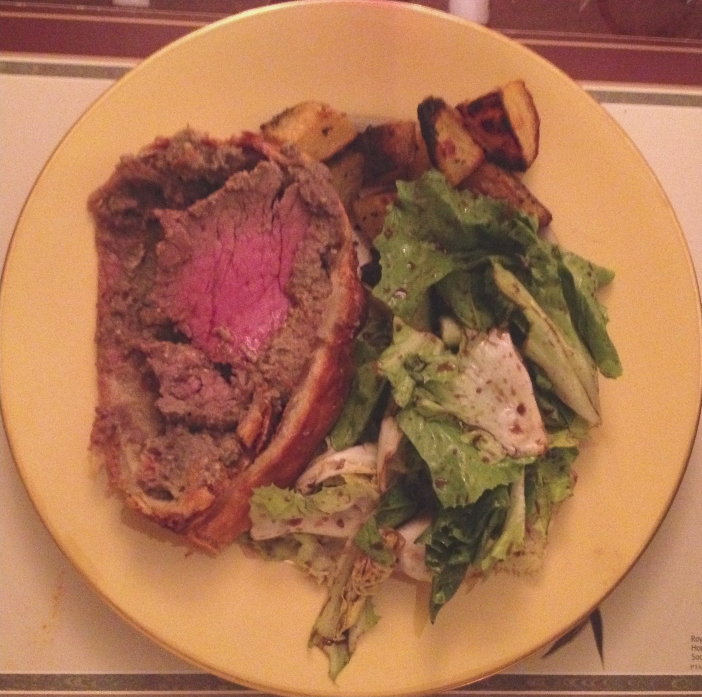 The main course plate - Beef Wellington, wilted escarole with a warm Balsamic dressing and crispy Yukon Gold potatoes.