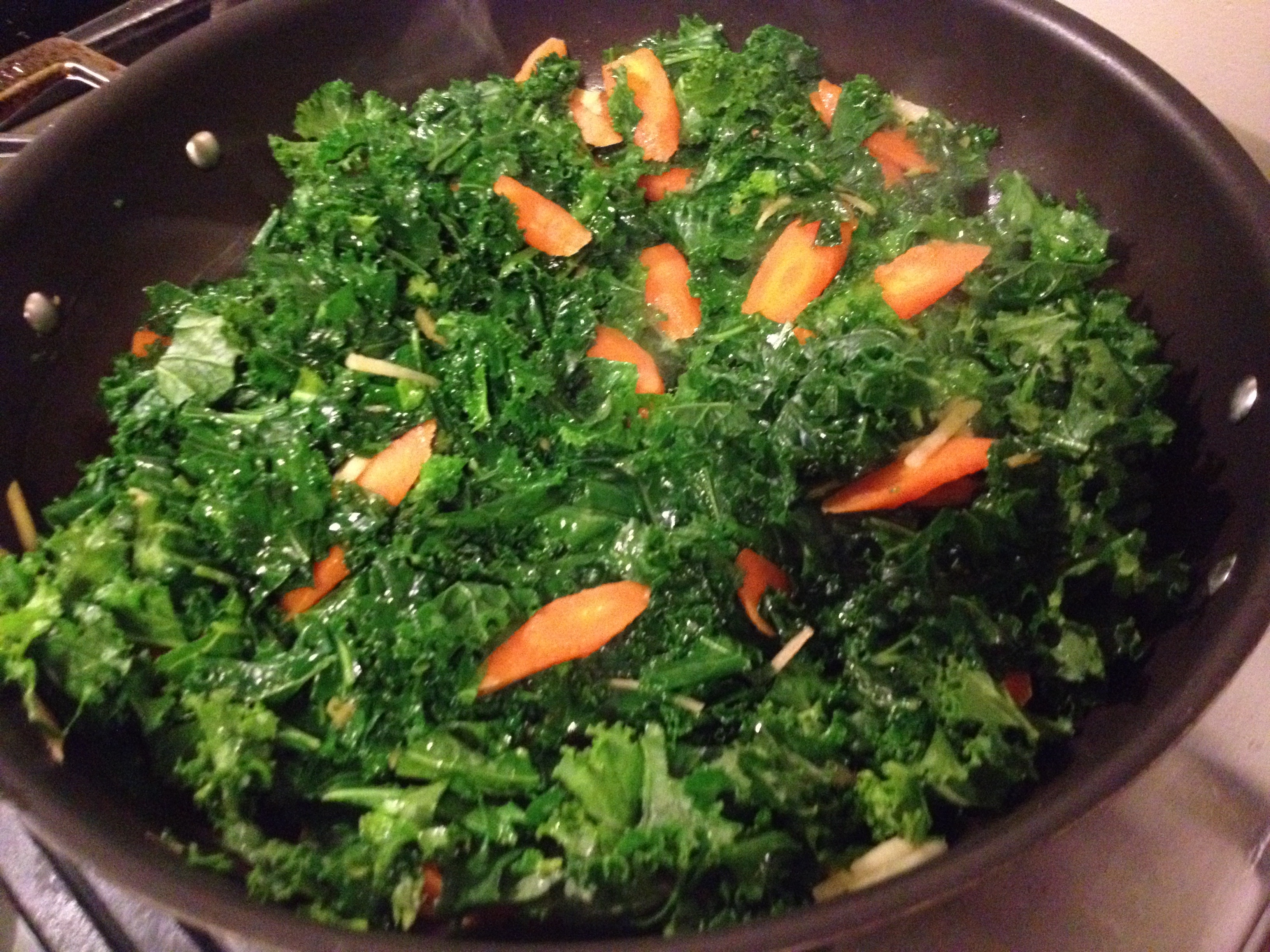 Kale with ginger and carrots and steam in a skillet.