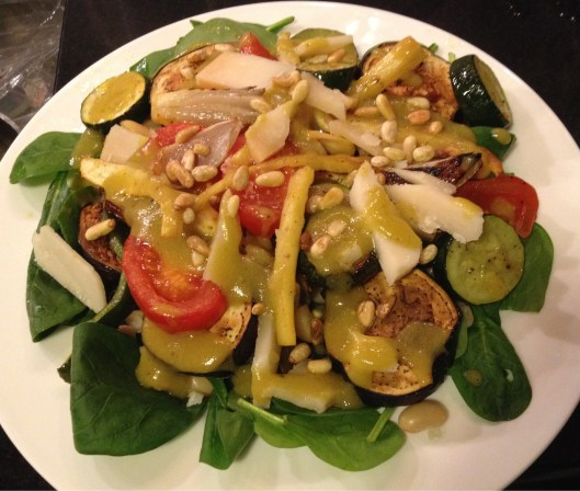 Vegetarian delight finished dish - baby spinach, beans and roasted vegetables topped toasted pine nuts and goat cheese.