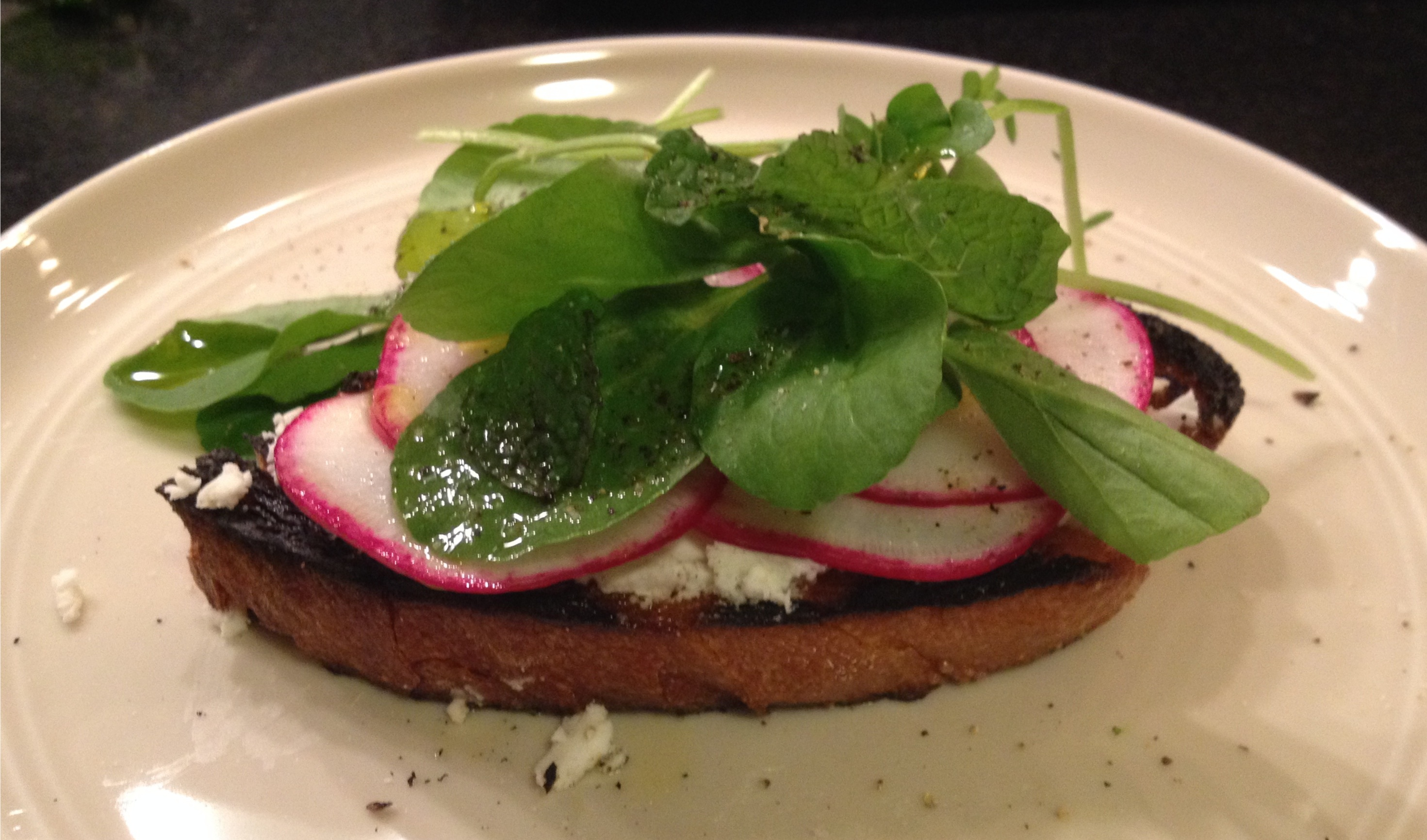 Feta radishes watercress and mint toasts serving on a plate.