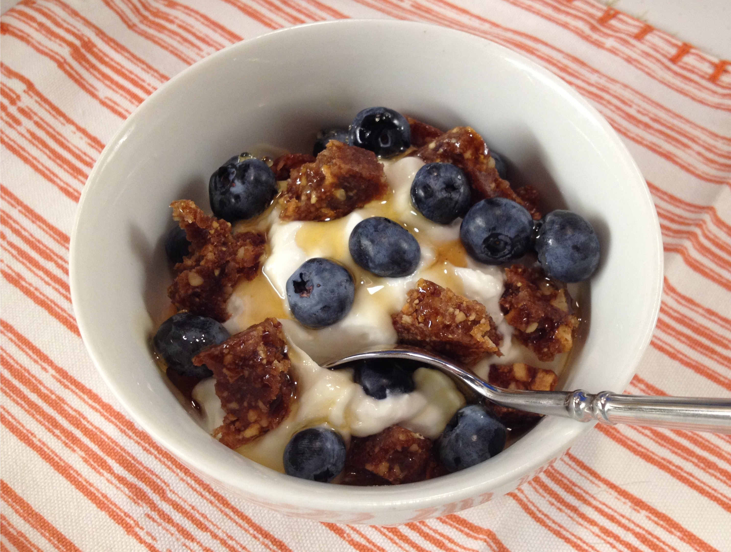 Plain Greek yogurt with coconut cashew bar bits blueberries and honey.