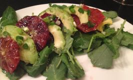 Blood orange, Avocado and baby kale salad on a white plate.