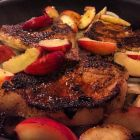 Pork chops with peaches in a skillet.