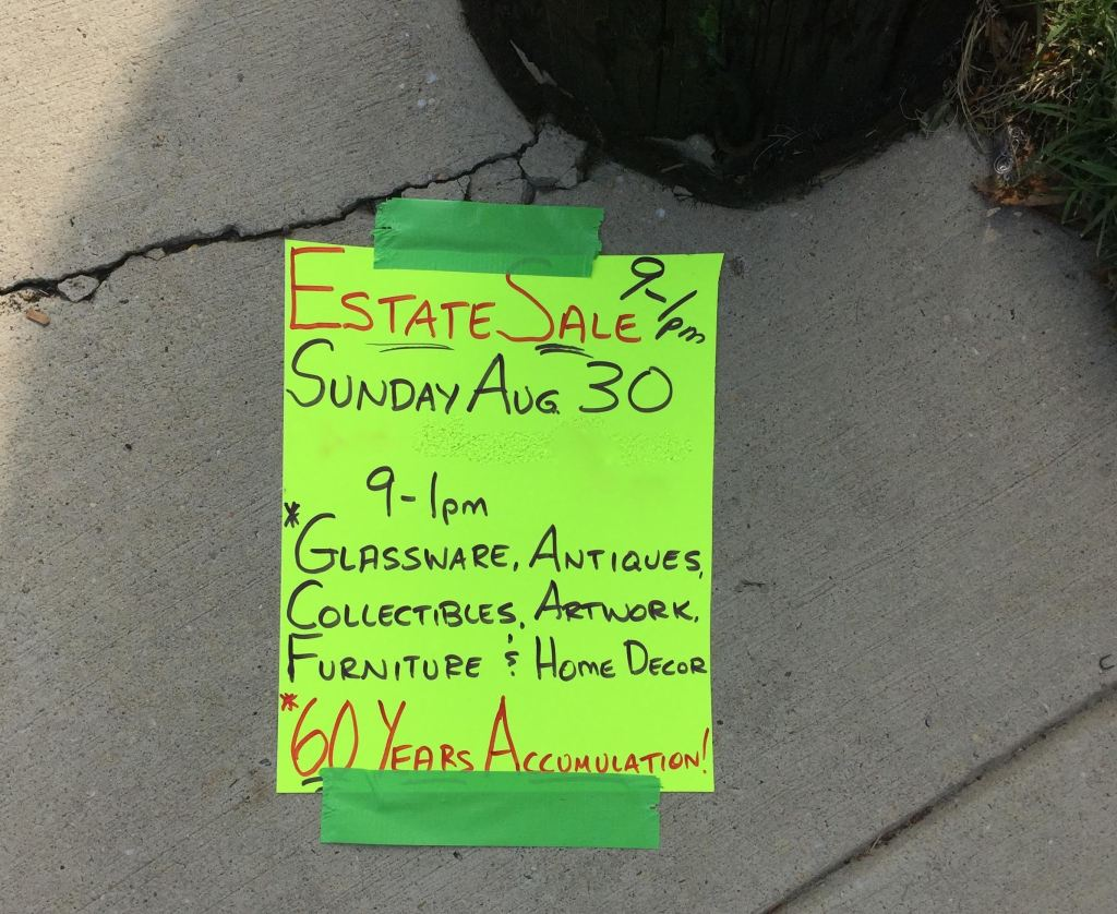 Estate sales sign on the sidewalk in Baltimore.