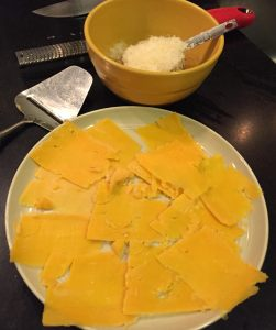Cheddar cheese slices and Parmigiano grated in a bowl.