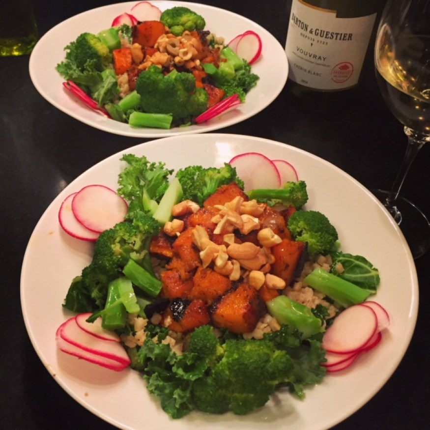 Kale and farro salad with spicy butternut squash, broccoli, radishes and cashews in two white bowls.