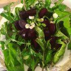 Arugula, roasted beet and scallion salad on an antique plate.