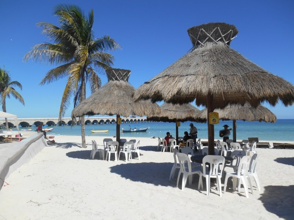 The palapa-lined beach near the pier at Progreso