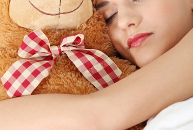 Charming brunette in bed with her teddy bear