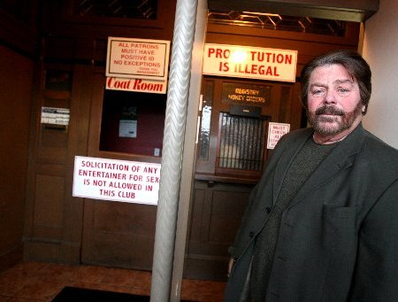 "Dick Shappy, owner of the Cadillac Lounge stands at the entrance to the club where signs are posted to notify guests that ""Prostitution is Illegal."" The Providence Journal/Frieda Squires"