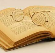 Old book, open, with eyeglasses laying on top