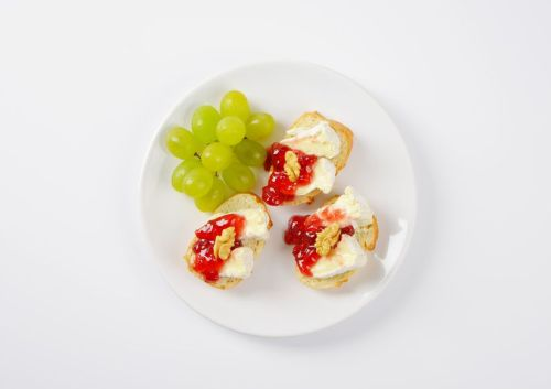 slices of fresh bread with brie cheese, walnuts, jam and grapes on white plate