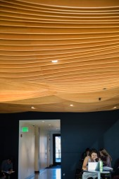 The new Coastal Biology building's relationship with the nearby ocean is made clear through wave decor that weaves and flows through the structure, including in the undulating wood waves lining the ceiling of the lobby.