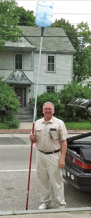 Dan Gray proudly displays his handy swarm grabber, fabricated from a heavy duty water jug and painter's extension pole.
