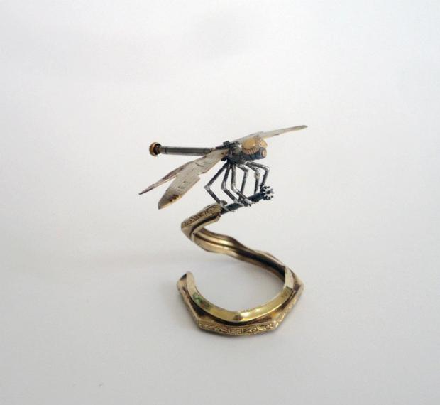 It's not all arachnids! This dragonfly is entirely soldered together, and rests on a winding stem attached to a watch case ring stand.