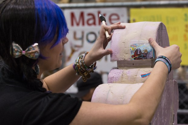 Artist Liz of Tracimoc glues down the first of many comic clippings, chosen and cut out by attendees, that will cover a foam Makey robot by the end of Maker Faire.