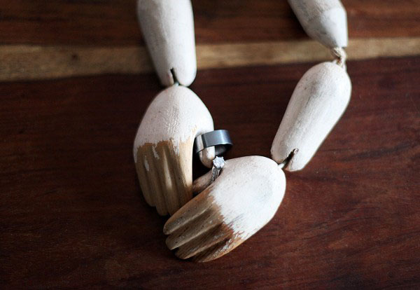 Small wooden hands hold the wedding bands.