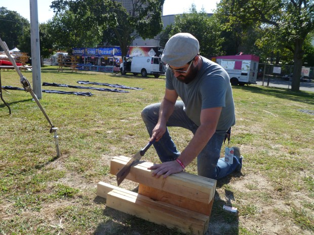 Brandon Regner designed and built Ford's display, featuring vintage drill presses employed as printers, and a stereo system made of old transistor radios. Here he is sawing away before the Faire starts.
