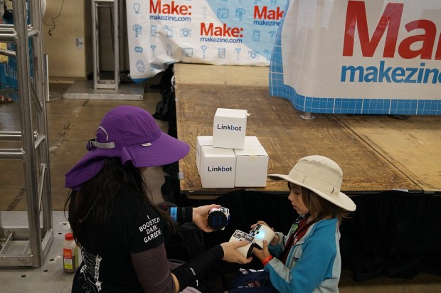 Girls discovering Linkbots at Maker Faire.