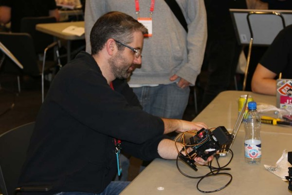 Jason Huggins, designer of the Dancebot, looking over one of the many robots at the workshop table.