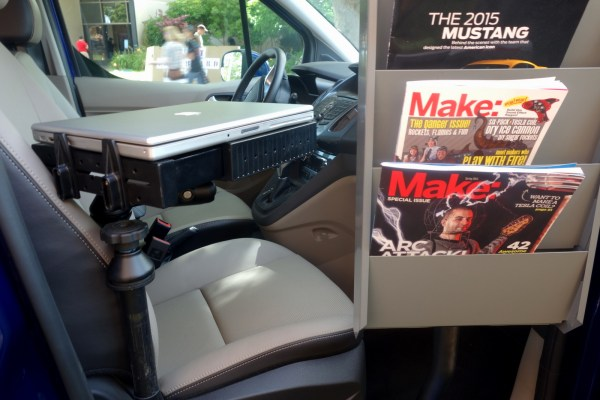Pipe-fittings along the door frame allow for various fixtures to be attached. Here a magazine rack displays copies of Make: along with a laptop swivel-station allowing for computer access in or outside the vehicle.