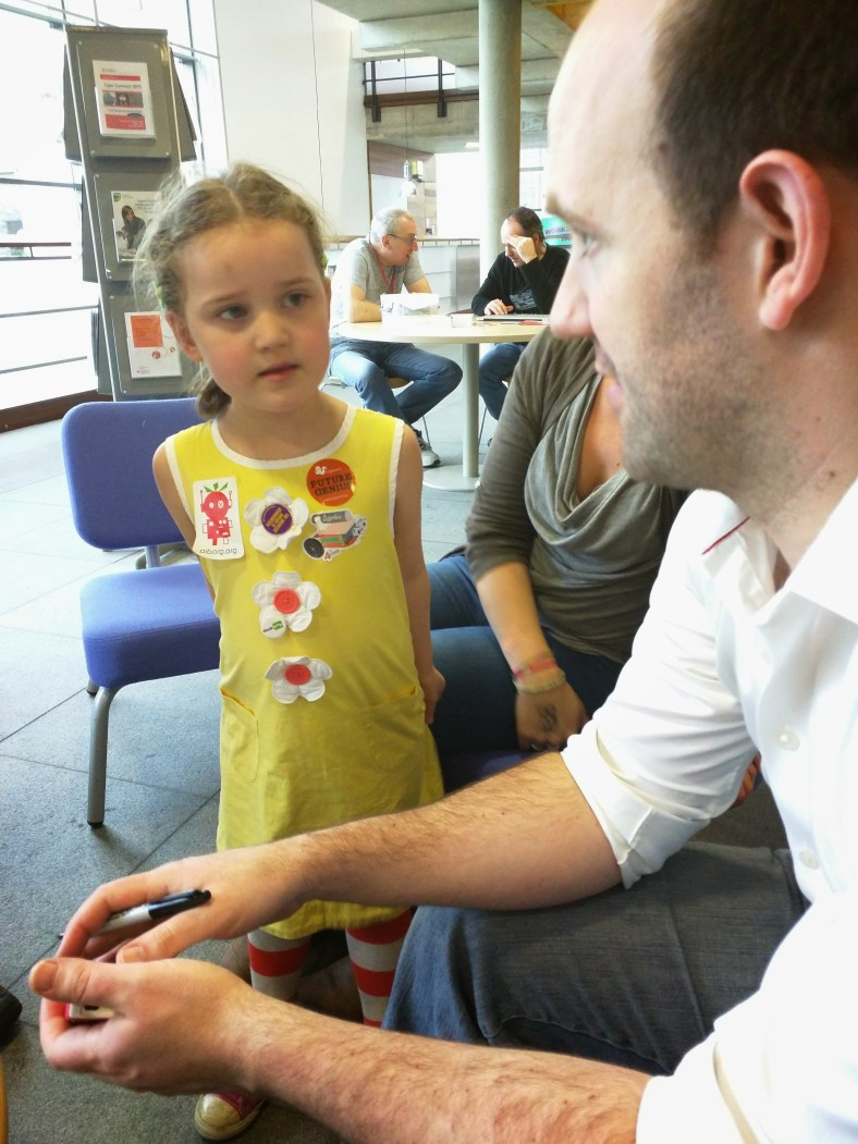 A young girl asks Eben Upton to autograph her Raspberry PI enclosure.