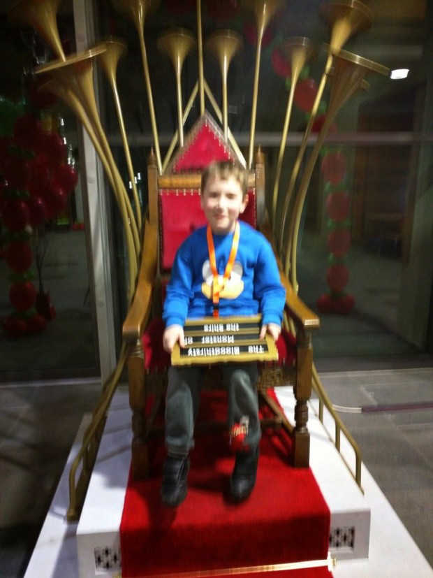 A young boy sits on the Talking Throne.