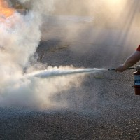 A man crouches down using a fire extinguisher to control a blaze.