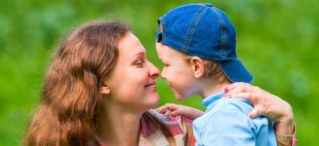 A little boy and his mother look at each other and laugh. Family composition