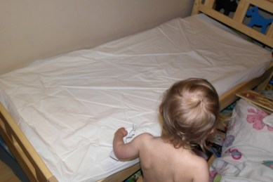 Her old crinkly plastic mattress protector