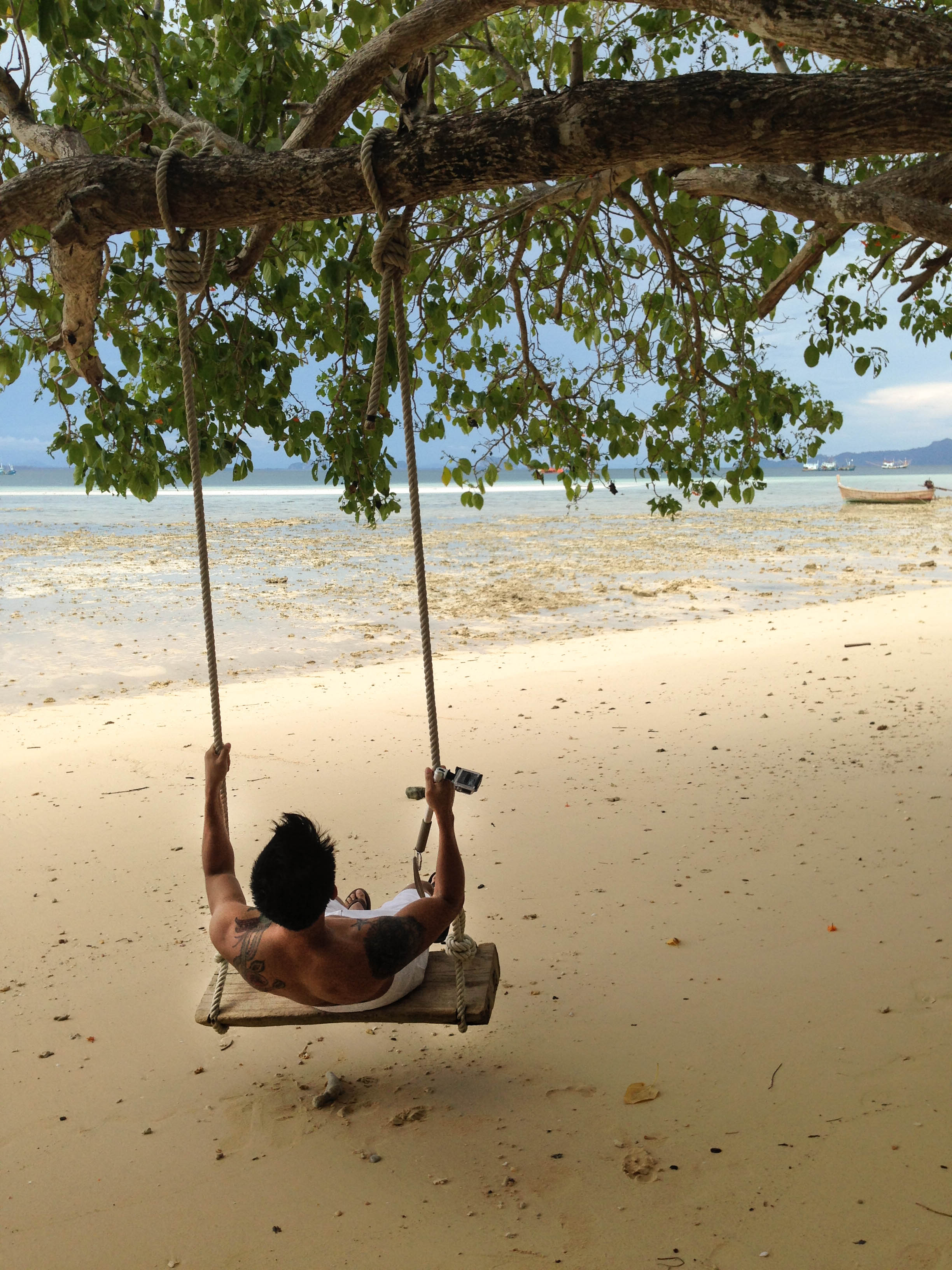 boy in swing on sandy beach on koh kradan island