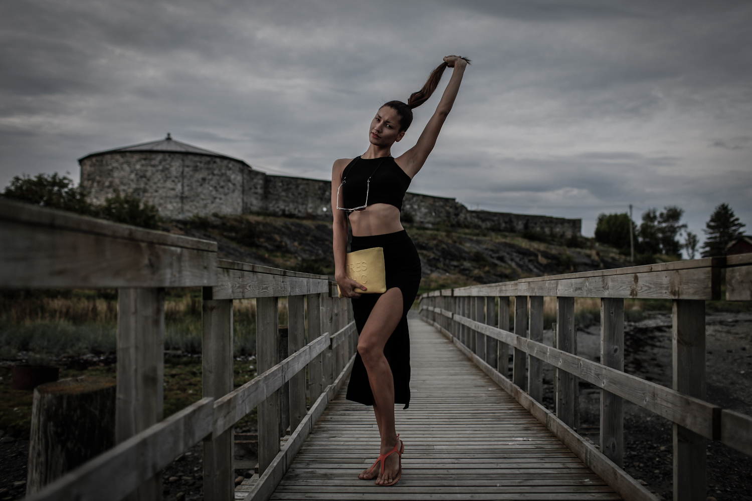 girl infront of steinvikholm castle wearing black dress and yellow bag