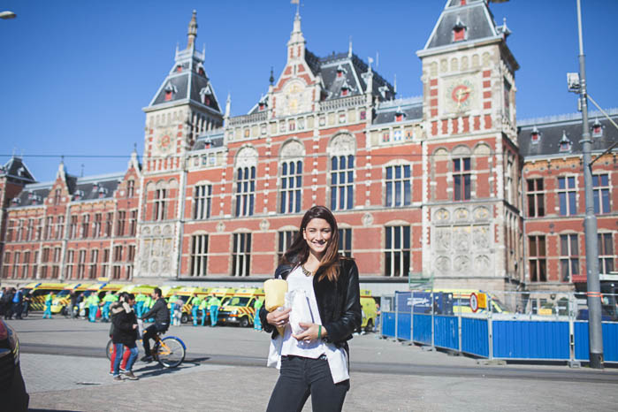 girl standing with baguette in from of centraal station