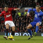 Manchester United's Ryan Giggs scores the opening goal past Everton's Phil Neville during their English Premier League soccer match at Old Trafford in Manchester