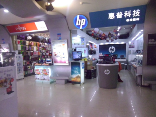 A picture of a stall selling HP computers next to a stall selling Fujitsu computers