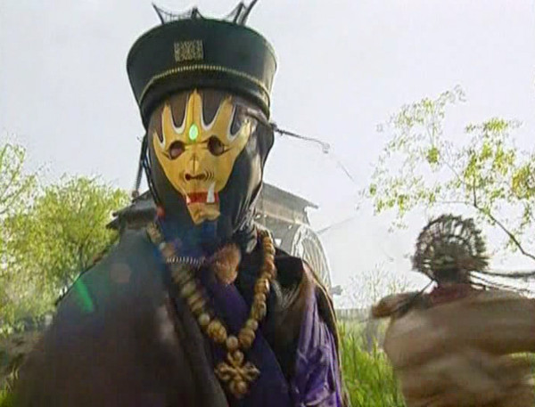 Yu Canghai wears a yellow mask in mid-fight.
