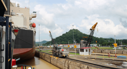"""There's very little room for vessel in front being guided through the Panama Cana's Pedro Miguel Locks. Rail cars equipped with cranes on the right are known as """"mules."""" They keep the vessel moving forward while inside the lock chamber. (Lorne Matalon)"""