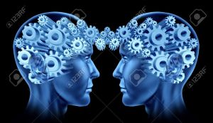 14119596-Teamwork-and-business-cooperation-with-two-human-heads-facing-each-other-with-gears-and-cogs-represe-Stock-Photo
